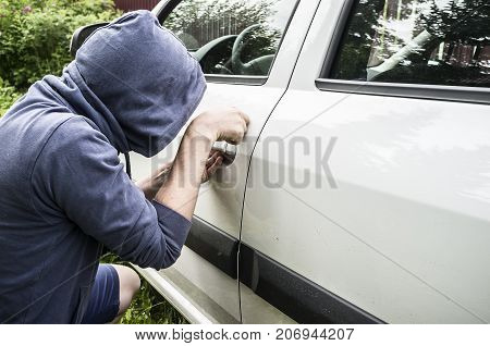 A man - a thief in a sweatshirt with a hood trying to steal a car and break a lock