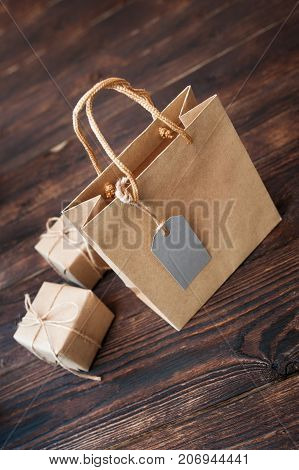Mockup Paper bag from kraft paper with gift tag and Christmas gift boxes on a wooden background.