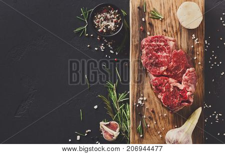 Raw rib eye steak with herbs and spices. Cooking ingredients for restaurant dish. Fresh meat, pepper salt, rosemary and garlic on wooden board at black background with copy space, top view