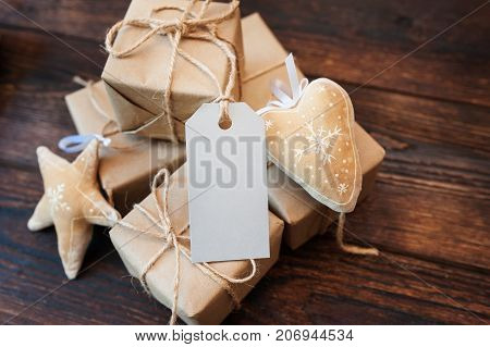 Mockup boxes for gifts of kraft paper and gift tags on a wooden background.