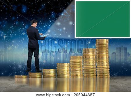 Asian Businessman standing on the stack of gold coins and using the tablet present the green screen over cityscape and star background Business virtual reality concept