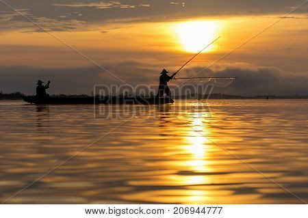 Silhouette of asia traditional fisherman in action when fishing at sunrise in the nature river at the early morning when senrise time