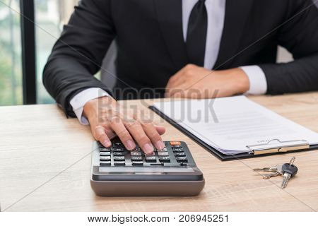 Hands of businessman pushing calculator for calculating a loan credit balance - financial concept