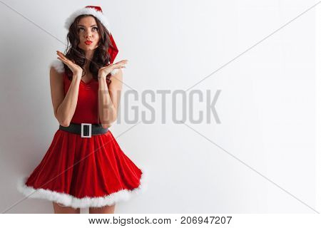 Pretty Pin-up style Santa girl in red hat on white background