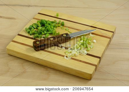 Chopped green onion scallions with green and white parts kept separate on cutting board with knife