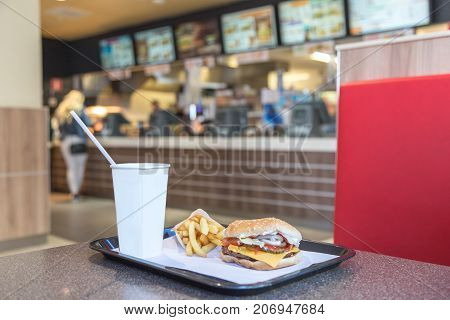 Burger, fries and cup for drink on a table in fast food restaurant.