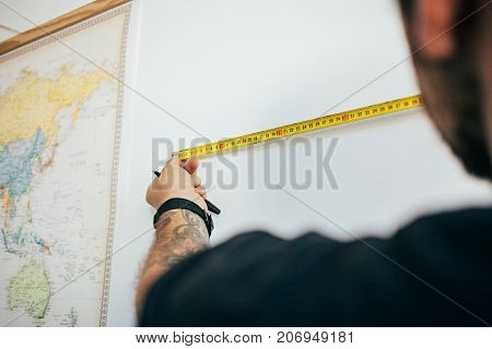 Close up soft focus of young man with arm tattoos uses measuring yellow tape next to world map hanging on wall chooses length and height of new place for painting or frame