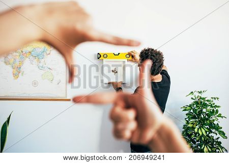 Young couple hangs frame or painting in new home on white wall next to world map woman puts her fingers in shape of square to frame how the photo will look