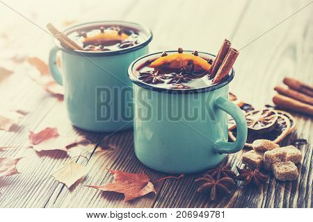 Mulled Wine In Blue Enameled Rustic Mugs With Spices And Citrus Fruits On Wooden Table With Autumn L