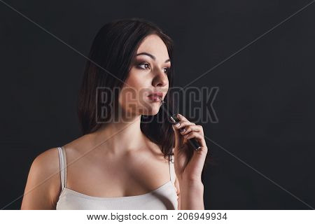 Girl with vape at black studio background closeup. Young woman smoking e-cigarette to quit tobacco. Nicotine free smoking and vapor concept, copy space