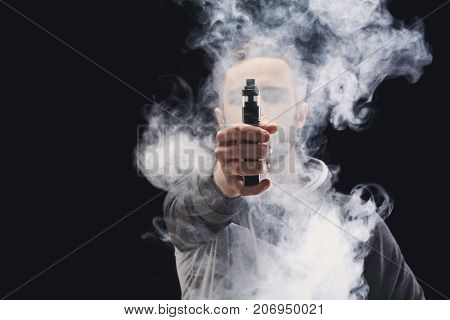 Unrecognizable man in the cloud of vape smoke. Guy smoking e-cigarette to quit tobacco. Nicotine free smoking and vapor concept, copy space