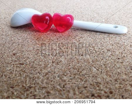Mini heart in white little spoon on plywood