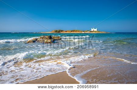 Typical summer image of an amazing pictorial view of a sandy beach with a boat on the beach and an old white church in a small island at the background, Malia, Crete, Greece.