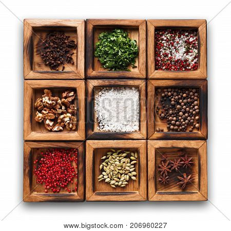 Spices assortment isolated on white background. Wooden boxes with flavorings. Salt, peppers, coriander seeds, cloves, walnuts and green parsley, cooking seasoning collection
