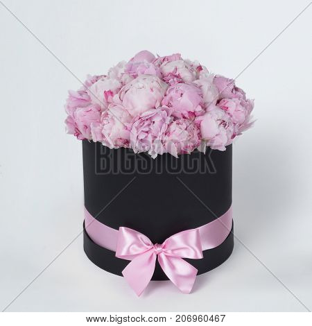 Luxury beautiful pink bouquet of peony flowers round black box with bow on gray background