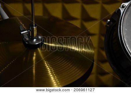Coppia di piatti con attacco, con un tamburo nello sfondo con luce poco diffusa, scura