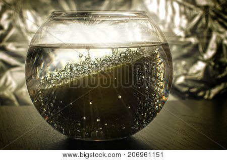 Lemon with bubbles in a transparent round vase with water, with a glare and rays in the background.