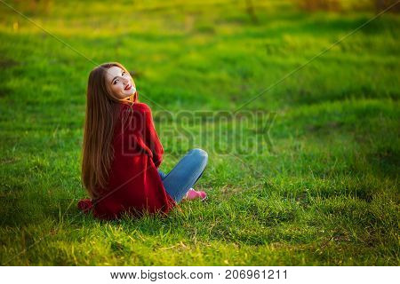 Portrait of happy sporty woman relaxing in park. Joyful female model breathing fresh air outdoors. Healthy active lifestyle concept