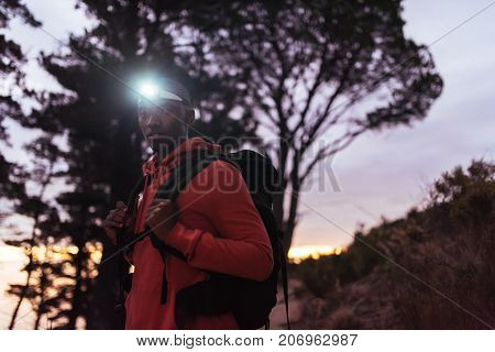 Portrait of a focused young African man wearing a headlamp standing alone in the forest while out for a cross country run at dusk