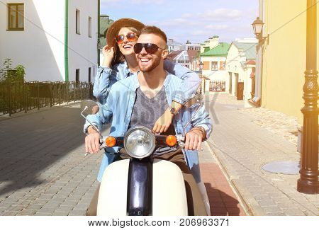happy young couple riding scooter in town. Handsome guy and young woman travel. Adventure and vacations concept
