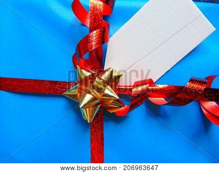Blue wrapped gift with blank tag and pretty shiny ribbon