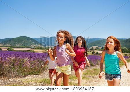 Group of four age-diverse girls, happy playmates, running one after another through lavender field in summer