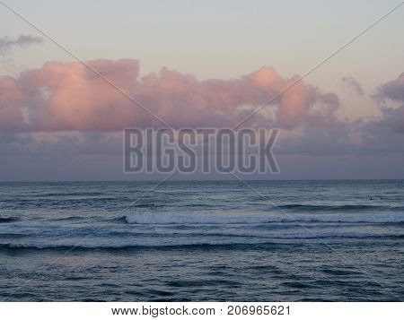 Beautiful pink and purple Dawn over the ocean with waves rolling towards the shore on the North Shore of Oahu with surfers in the water.