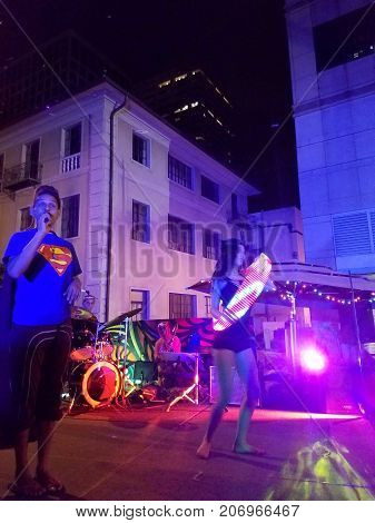 Honolulu - October 29 2016: Jerome James on the mic with Lady spins LED hula hoop as people dance on stage as part of Activ8 Electro Jazz Circus at Hallowbaloo as crowd watches.