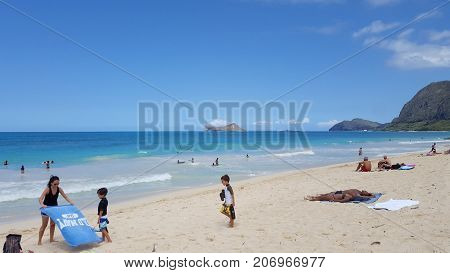 WAIMANALO - May 29 2016: People play in water and sunbath as Gentle wave lap on Waimanalo Beach looking towards Rabbit island and Rock island on a nice day Oahu Hawaii. May 29 2016