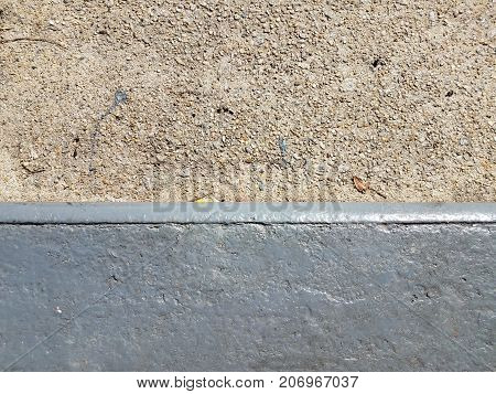 a grey cement sidewalk with a painted curb