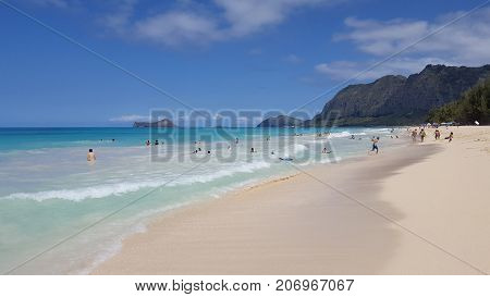WAIMANALO - May 29 2016: People play in water Gentle wave lap shore on Waimanalo Beach looking towards Rabbit island and Rock island on a nice day Oahu Hawaii. May 29 2016