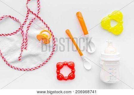 preparation of mixture baby feeding with infant formula powdered milk in bottle with bib on white desk background top view