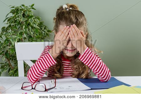 Cute junior schoolgirl with blond hair smiling drawing in a school notebook and having fun at home at a table