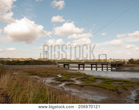 Old Unused Bridge In The Distance Above Estuary Stream Countryside
