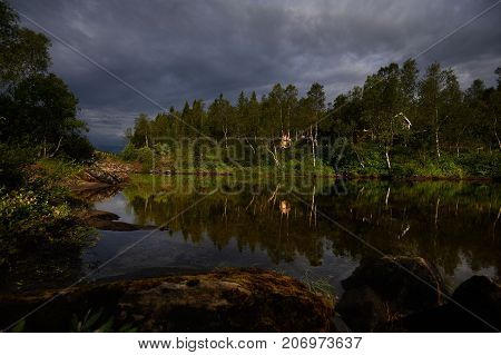 Landscape before thunderstorm with dark clouds and reflection