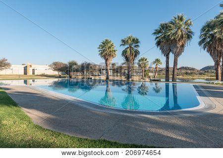 GROSS BARMEN NAMIBIA - JULY 4 2017: A swimming pool with the restaurant in the back at Gross Barmen near Okahandja in the Otjozondjupa Region of Namibia