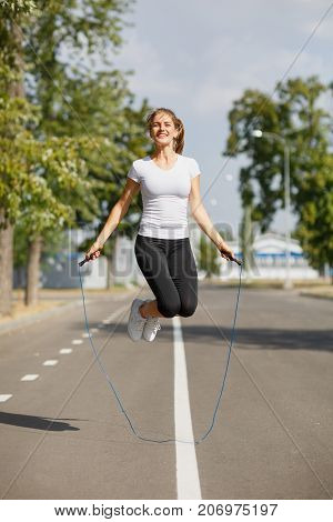 Joyful and attractive young girl jumping on a jump-rope on a blurred park background. Legs exercise and workout outdoors. Copy space.