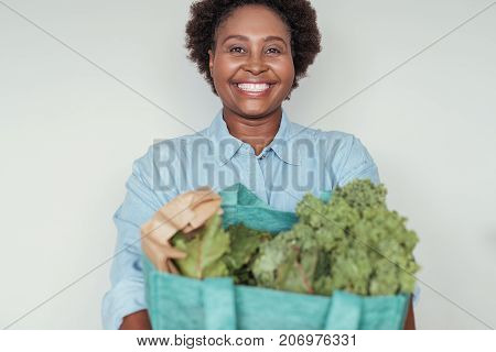 Smiling young African woman standing alone at home after shopping holding a bag full of fresh produce