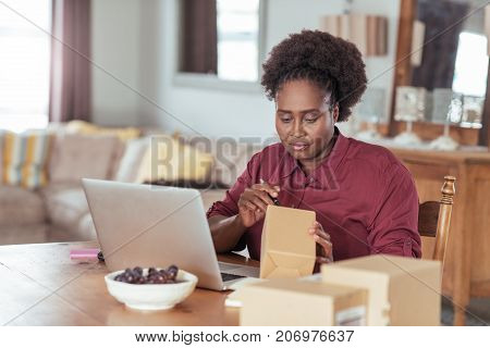 Young African woman sitting at a table at home using a laptop and writing addresses on packages for her home based online business