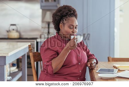 Young African woman sitting alone at her kitchen table at home drinking a cup of coffee and working on a digital tablet