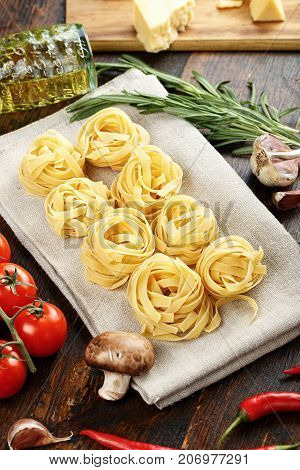 raw tagliatelle with tomatoes asparagus beans mushrooms on a wooden background