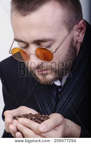 man holds grains of coffee in hands