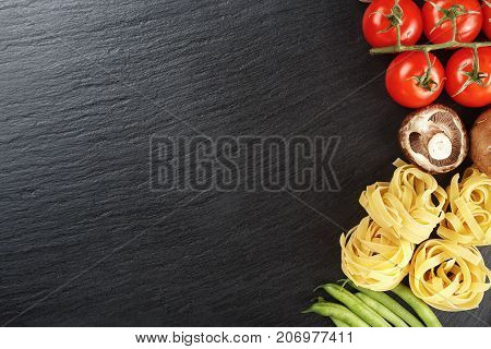 raw tagliatelle pasta with vegetables on a black background space for text