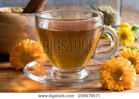 Calendula Tea And Calendula Flowers On A Wooden Table