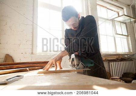 Carpenter cutting wooden board on workbench with handle circular saw. Entrepreneur working on his small woodworking venture. Woodworker works on local lumber production or custom furniture manufacture