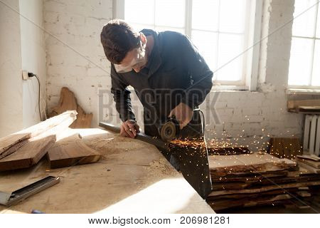 Craftsman in protective glasses cutting steel plank on workbench with angle grinder in workshop. Cabinet maker working on a new project. Starting own small home-based manufacturing business concept
