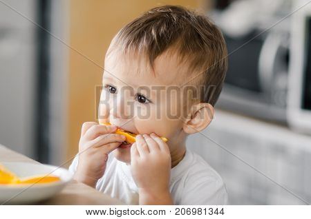 The Child In The Kitchen Eating An Orange