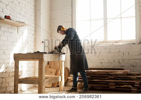 Artisan in protective glasses and headphones working with angle grinder in carpentry. Young guy has part time small business opportunity in local workshop. Skilled workforce for manufacturing concept