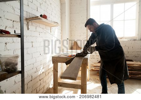 Skilled carpenter with handsaw cutting wooden plank in workshop interior. Young craftsman holding arm saw sawing board on workbench table, using woodworking tools. Carpentry and construction concept