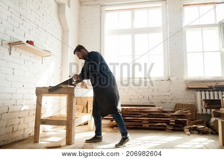 Young trained carpenter working in his carpentry shop, woodworker cutting wooden plank with handsaw for custom-made furniture. Skilled craftsman sawing wood board on table using portable arm saw